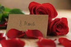Três rosas vermelhas e pétalas na tabela de madeira velha com o cartão de papel do 8 de março Imagens de Stock Royalty Free