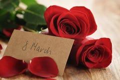 Três rosas vermelhas e pétalas na tabela de madeira velha com o cartão de papel do 8 de março Imagem de Stock Royalty Free