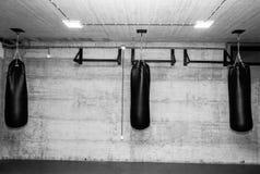 Três sacos de perfuração pretos no gym vazio do encaixotamento com a parede despida do grunge no fundo preto e branco imagem de stock