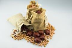 Três sacos de serapilheira, foram enchidos com os amendoins, as datas vermelhas e os feijões vermelhos Fotografia de Stock Royalty Free