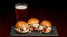 Três sanduíches do slider em uma placa da ardósia com uma cerveja gelado Foto de Stock Royalty Free