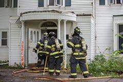 Três sapadores-bombeiros na cena do fogo que andam em uma construção Fotografia de Stock Royalty Free