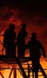 Três sapadores-bombeiros que conferem Fotografia de Stock