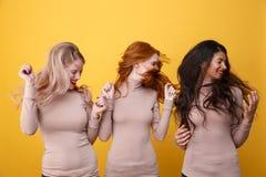 Três senhoras felizes que agitam o cabelo Fotos de Stock Royalty Free
