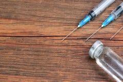 Três seringas médicas e Vial On Rough Wood Board imagem de stock