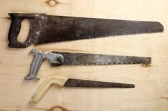 Três serras que encontram-se em uma folha da madeira compensada vintage Imagem de Stock