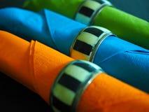 Três serviettes coloridos em anéis de guardanapo Imagem de Stock Royalty Free