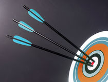 Três setas do tiro ao arco do preto azul bateram em volta do centro do Bullseye do alvo fotografia de stock
