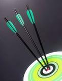 Três setas pretas verdes do tiro ao arco bateram em volta do Bullseye Cente do alvo Imagens de Stock