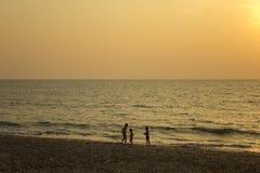 três silhuetas escuras das crianças na areia amarela da praia contra o mar e a noite foto de stock