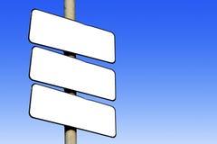 Três sinais brancos vazios contra um fundo azul Imagem de Stock