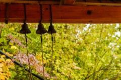 Três sinos pequenos penduram em feixes de madeira marrons fotografia de stock royalty free