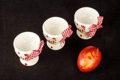 Três suportes e ovos da páscoa de ovo no fundo preto Imagem de Stock Royalty Free