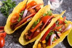 Três tacos mexicanos coloridos nos shell no fundo de pedra fotografia de stock