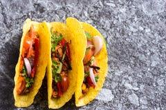Três tacos mexicanos coloridos nos shell no fundo de pedra fotografia de stock royalty free
