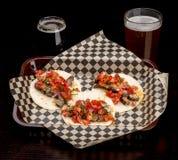 Três tacos pequenos e dois vidros da cerveja fazem um almoço Imagens de Stock Royalty Free