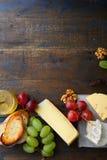 Três tipos de queijo com uvas, mel, pão e nozes Fundo vazio do espaço Fotos de Stock Royalty Free