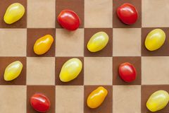 Três tipos de tomates de cerejas maduros coloridos em um tabuleiro de xadrez, vista superior, alimento saudável, estilo de vida d Fotografia de Stock