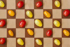 Três tipos de tomates de cerejas maduros coloridos em um tabuleiro de xadrez, vista superior Conceito do vegetariano, dieta, desi Fotografia de Stock