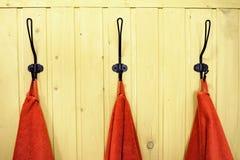 Três toalhas vermelhas em ganchos na parede de madeira amarela imagens de stock royalty free