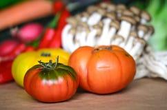Três tomates com outros alimentos Imagens de Stock
