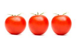 Três tomates maduros vermelhos no fundo branco Imagem de Stock