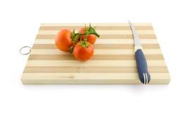 Três tomates no ramo verde na mesa com isolat da faca Fotos de Stock