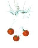 Três tomates que caem na água Fotos de Stock Royalty Free