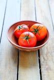 Três tomates vermelhos maduros em uma bacia Fotografia de Stock Royalty Free