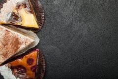 Tr?s tortas caseiros em uma tabela preta, espa?o da c?pia fotografia de stock