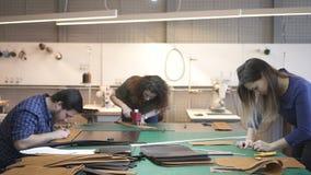 Três trabalhadores de couro que fazem detalhes do saco no estúdio vídeos de arquivo