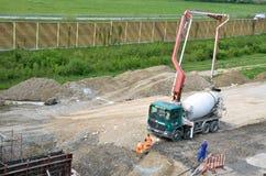 Três trabalhadores e caminhão concreto do transporte com bomba concreta de modo operacional Esta atividade é relacionada ao PR ra Fotografia de Stock Royalty Free