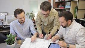 Três trabalhadores que discutem o projeto do negócio que está no escritório Os colegas de trabalho trabalham junto Conceito da re filme