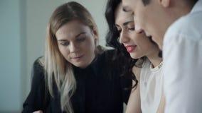 Três trabalhadores sentam-se perto e discutem-se perguntas dentro do escritório filme