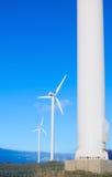 Três turbinas de vento, céu azul. Fotos de Stock