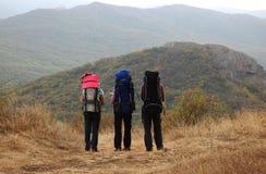 Três turistas com trouxas estão em uma inclinação de montanha Fotografia de Stock