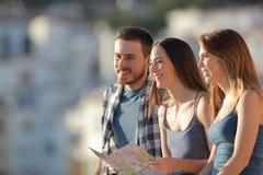 Três turistas que contemplam vistas em uma cidade foto de stock royalty free