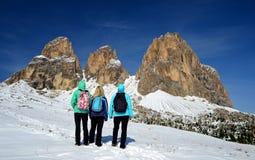Três turistas que olham a montanha bonita agrupam Sassolungo Langkofel imagem de stock