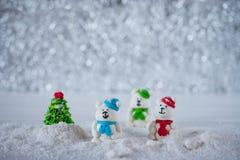 Três ursos dos doces de açúcar na neve no fundo do bokeh com espaço da cópia para o cumprimento da estação Foto de Stock Royalty Free