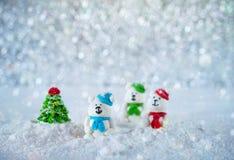 Três ursos dos doces de açúcar na neve no fundo do bokeh com espaço da cópia pelo Feliz Natal do cumprimento da estação ou o ano  Foto de Stock Royalty Free