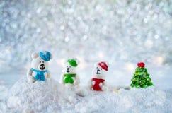 Três ursos dos doces de açúcar na neve no fundo do bokeh com espaço da cópia pelo Feliz Natal do cumprimento da estação ou o ano  Fotos de Stock