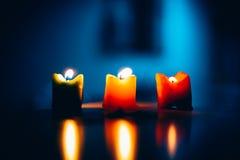 Três velas ardentes em seguido com fundo azul imagem de stock
