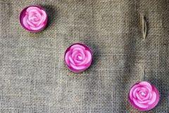 Três velas bonitas da cera cor-de-rosa sob a forma das flores cor-de-rosa com um feltro de lubrificação unbaked no fundo de uma l imagens de stock