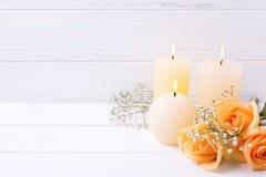 Três velas e pêssegos ardentes colorem flores das rosas no wo branco Fotos de Stock