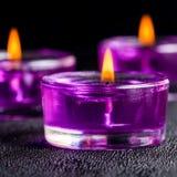 Três velas roxas bonitas em um fundo preto com água Fotografia de Stock