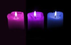 Três velas, roxos e azuis Imagem de Stock