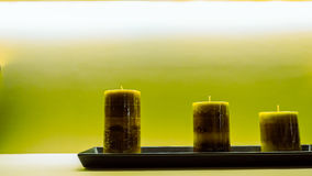Três velas verdes na bandeja plástica preta puseram sobre a tabela branca Imagens de Stock Royalty Free