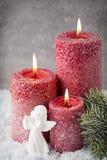 Três velas vermelhas no fundo cinzento, decoração do Natal Adve Imagens de Stock