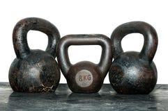 Três velhos e sinos da chaleira da oxidação no assoalho do gym Fotografia de Stock Royalty Free