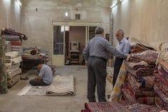 Três vendedores do tapete que discutem e que rezam em uma loja do tapete no bazar de Yazd Khan Os tapetes são das exportações icó imagem de stock